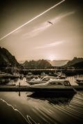 yachts and boats near moorage at sunset in reine village, norway - stock photo