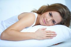 Pretty Woman Lying Prone on White Pillow Stock Photos
