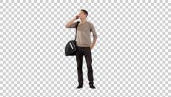 Young man standing with bag and calling by phone Stock Footage