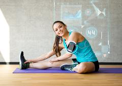 smiling woman stretching leg on mat in gym - stock illustration