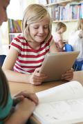 elementary school pupil using digital tablet in classroom - stock photo
