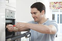 Repairman fixing domestic oven in kitchen Stock Photos