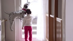 Little girl with helium balloon knocking on a glass door - stock footage