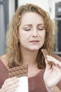 guilty woman on diet eating chocolate bar at home - stock photo