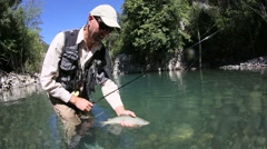 closeup of fly fisherman releasing trout in river - stock footage