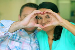 Happy couple making heart to the camera and smiling, steadycam shot - stock footage