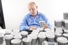 Overworked businessman drinking too much coffee Stock Photos
