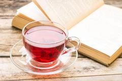 Literature background. Cup of hot tea with opened book - stock photo