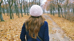 Lonely woman in coat and beret is one in the autumn forest Stock Footage