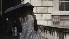 Girl with a black umbrella, walking in the rain Stock Footage