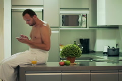 Man after shower in the towel looking on smartphone and sitting in the kitchen Stock Footage