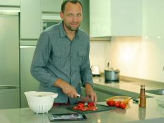 Man cutting tomato in the kitchen and smiling to the camera Stock Footage