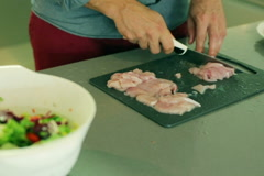 Man cutting chicken on the chopping board in the kitchen Stock Footage