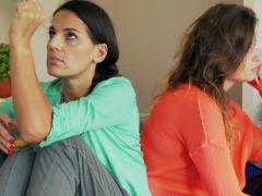 Female friends after quarrel sitting on the sofa and doing faces Stock Footage