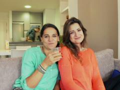 Female friends making toast to the camera on the sofa Stock Footage