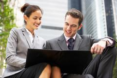 Businessman and businesswoman discussing document outside office Stock Photos