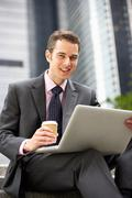 Businessman working on laptop outside office with takeaway coffee Stock Photos