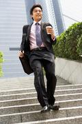 Chinese businessman rushing down steps carrying bag and takeaway coffee Stock Photos