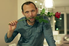 Happy man with rose and wine flirting to the camera - stock footage