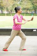 Senior chinese woman doing tai chi in park Kuvituskuvat