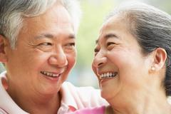 head and shoulders portrait of a senior chinese couple - stock photo