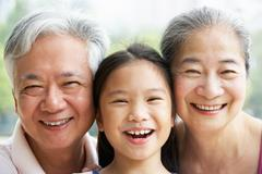 Head and shoulders portrait of chinese grandparents with granddaughter ride Stock Photos