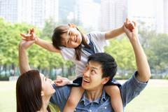 Chinese family giving daughter ride on shoulders in park Kuvituskuvat