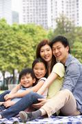 Young chinese family relaxing in park together Kuvituskuvat