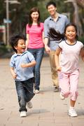 Chinese family walking through park with running children Stock Photos