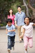 Chinese family walking through park with running children Kuvituskuvat