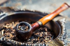 closeup of old wooden pipe in an ashtray - stock photo