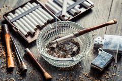 glass ashtray with thin wooden pipes, cigarettes and lighter around - stock photo