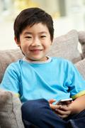 Young chinese boy using mobile phone on sofa at home Stock Photos