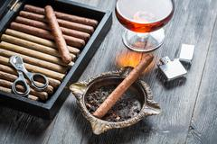 Cigar in ashtray, lighter and cognac Stock Photos