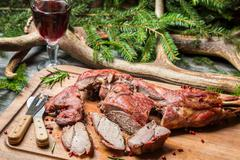 fresh venison around with antlers and spruce - stock photo