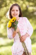 Young girl walking through summer field holding sunflower Stock Photos