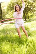 young girl walking playing with hula hoop in summer field - stock photo