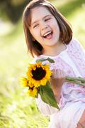 Young girl sitting in summer field holding sunflower Stock Photos