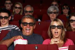 Couple watching 3d film in cinema Stock Photos