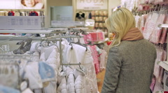 Woman in shop, chooses clothes, baby store Stock Footage