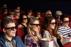 Group of teenage friends watching 3d film in cinema Stock Photos