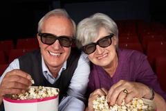 Senior couple watching 3d film in cinema Stock Photos