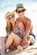 Teenage couple enjoying beach holiday together Stock Photos