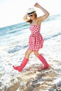 Teenage girl wearing wellington boots splashing in sea on beach holiday Stock Photos
