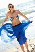 Teenage girl wearing sarong on beach holiday Stock Photos