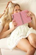 Woman sitting on sofa reading diary Stock Photos