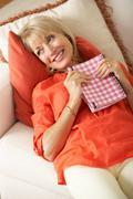 Senior woman sitting on sofa reading diary Stock Photos