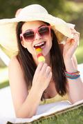 woman relaxing in garden eating ice lolly - stock photo