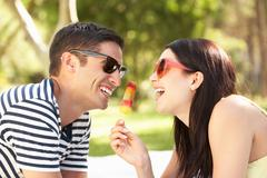 Couple relaxing together in garden eating ice lolly Stock Photos