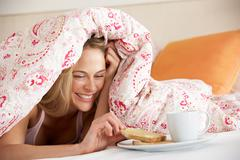 Pretty woman snuggled under duvet eating breakfast Stock Photos